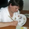 A woman is painting plate of Herend porcelain