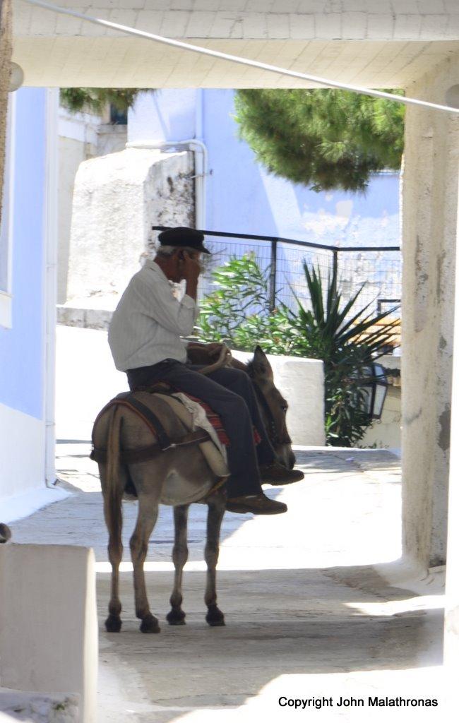 Farmer on donkey with mobile phone, Ioulida, Kea