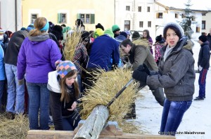 Hom Strom scuol Switzerland everyone is helping to wind the straw
