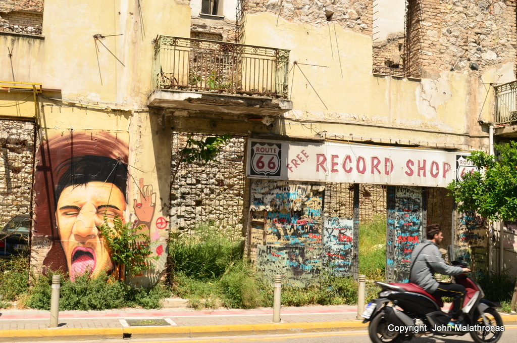 Graffiti in front of the ruins of a record shop at Patras Greece